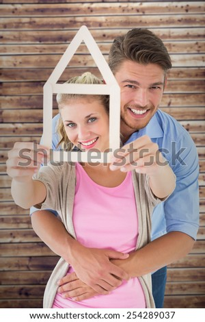 Young couple hugging and holding house outline against wooden planks - stock photo