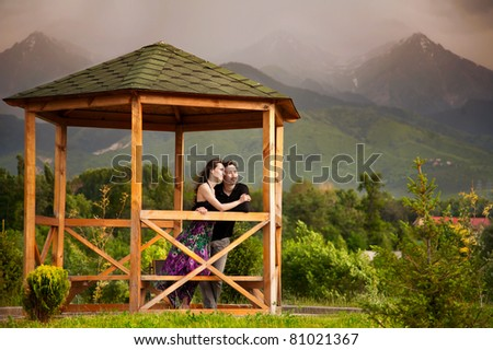 Young couple hugging and looking somewhere in summer house at mountains and hills background - stock photo