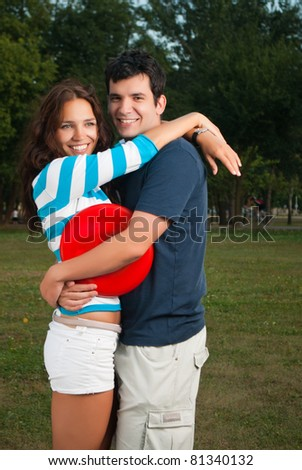 Young couple hugging and posing in park - stock photo