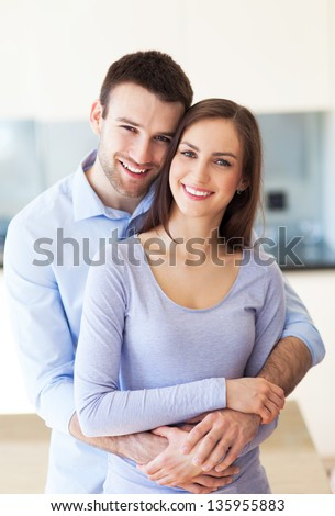 Young couple hugging at home - stock photo