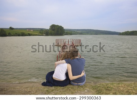 Young couple hugging during sunset hours. Strong wind blowing. - stock photo