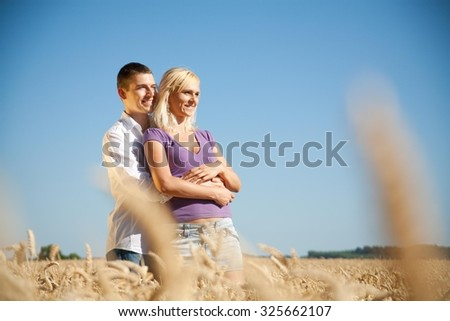 Young couple hugging in a wheat field - stock photo
