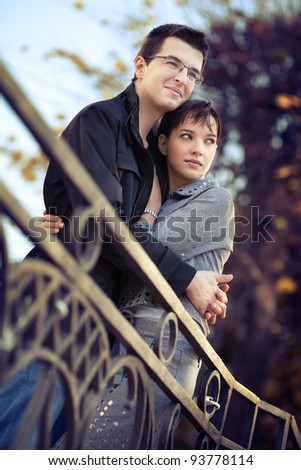 Young couple hugging in the autumn park and looking to a bright future - stock photo