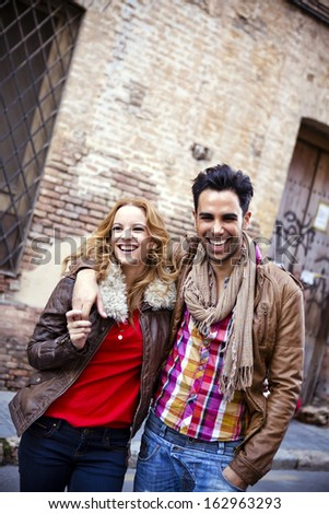 Young couple in a candid shot. They are walking in the street. - stock photo