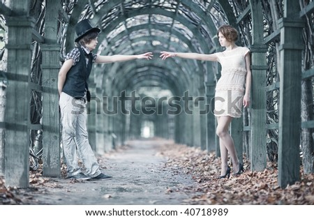 Young couple in a park stretching hands. Shallow dof effect. - stock photo