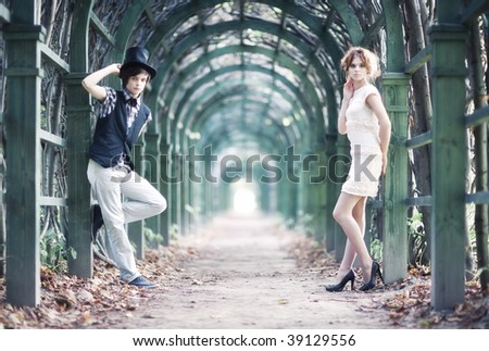 Young couple in a park with long passage. - stock photo