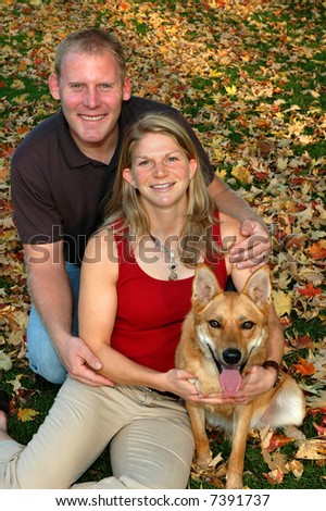 young couple in autumn leaves with their dog - stock photo