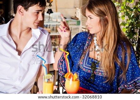 young couple in cafe in conversation, outdoor shot - stock photo