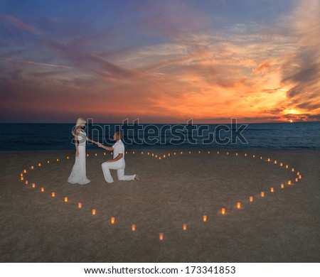 Young couple in candles heart at sea beach against sunset- St.Valentines Day romantic concept - stock photo