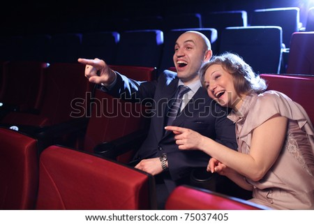 Young couple in cinema movie theater laughing while watching comedy show. - stock photo