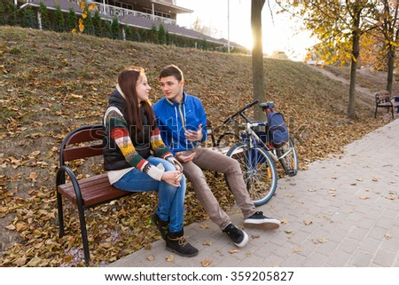 Young Couple in Conversation Sitting Together on Bench Next to Bicycle in Urban Park with Bright Setting Sun in Background on Chilly Autumn Day - stock photo