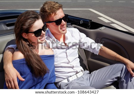 Young couple in dark sunglasses sits having embraced in a cabriolet on back seats - stock photo