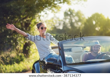 Young couple in his convertible car, happy to drive on a country road in summer.Shot with flare - stock photo