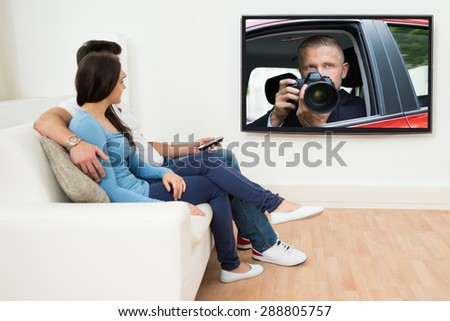 Young Couple In Livingroom Sitting On Couch Watching Television - stock photo