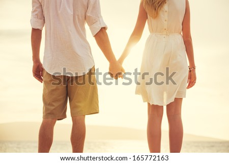 Young couple in love, Attractive man and woman enjoying romantic evening on the beach, Holding hands watching the sunset - stock photo