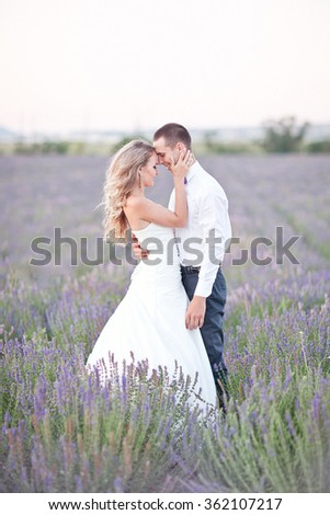 Young couple in love bride and groom, wedding day in summer. Enjoy a moment of happiness and love in a lavender field. Bride in a luxurious wedding dress. Summer mood and freedom. - stock photo
