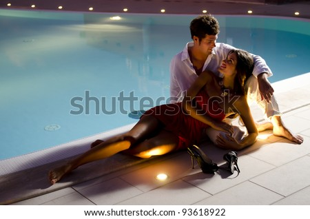 Young couple in love by the pool - stock photo