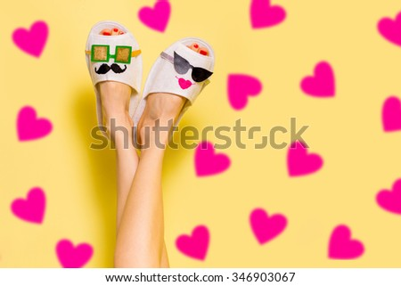 Young couple in love concept. Woman in funny slippers creative idea over heart background - stock photo