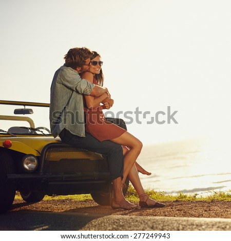 Young couple in love embracing and kissing. Young man and woman sitting on their car hood. Romantic young couple on road trip. - stock photo