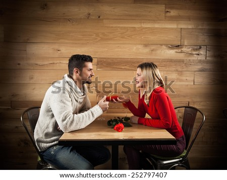Young couple in love exchanging gifts for Valentine's Day in a restaurant - stock photo