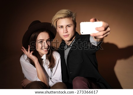 young couple in love hipsters in the studio wearing hats, love, youth, relationships, teenagers, pictures of themselves - stock photo