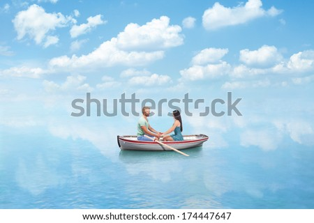 young couple in Love hold hands on boat in sea - stock photo