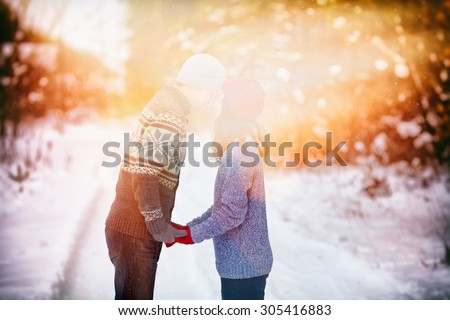 Young couple in love holding hands outdoor in winter at sunset - stock photo