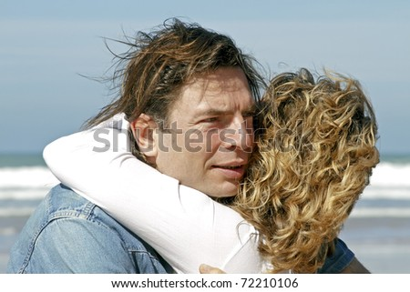 Young couple in love hugging each other at the beach - stock photo