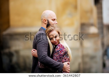 Young couple in love, hugging on the street. Selective focus. bald guy with a beard - stock photo