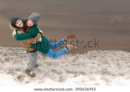 young couple in love, hugging, smiling.  Women in motion, jump. Outdoors - stock photo