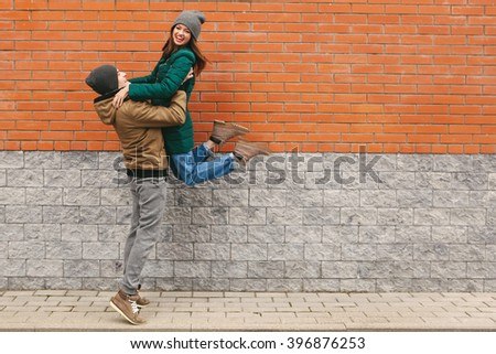 young couple in love, hugging, smiling.  Women in motion, jump. Outdoors. Brick background. copyspace - stock photo