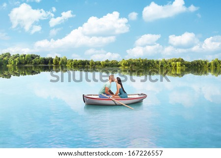 young couple in Love kisses on boat on lake - stock photo