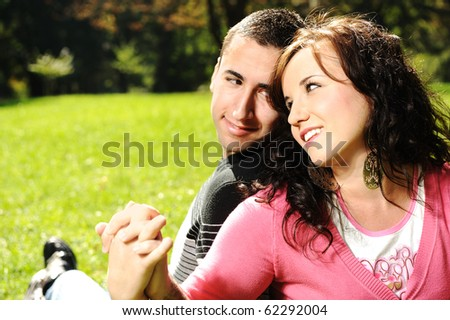 Young couple in love: lovers in park holding each other's hands and smiling - stock photo