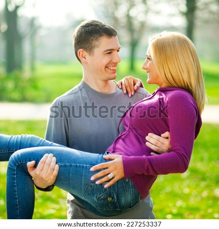 Young couple in love, man holding a woman in his arms - early spring field as a background - stock photo