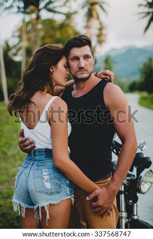 young couple in love, motorcycle, hugs, passion, free spirit, vintage, hipster, romantic, tropic vacation, honey moon, cool outfit, modern style, rock, sexy denim, run away, hugging, embrace, shorts - stock photo