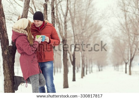 Young couple in love on a winter vacation, standing next to a tree, chatting and drinking hot cup of tea - stock photo