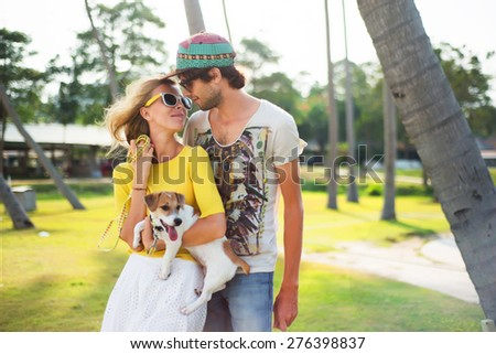 Young couple in love on park opposite the palm trees, summer sunny evening,with dog. Summer mood,summer beach portrait of young couple in love,wearing sunglasses, cap, yellow shirt, island romance  - stock photo