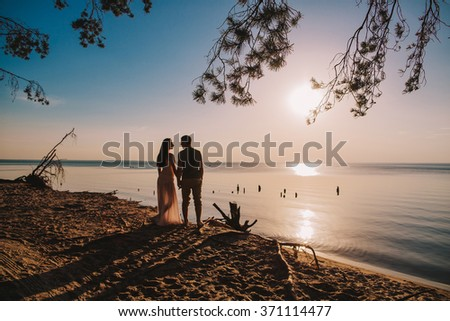 Young couple in love on summer sunny evening. at sunset on the beach - stock photo