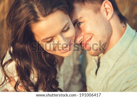 Young couple in love outdoor.Stunning sensual outdoor portrait of young stylish fashion couple posing in summer in field.Couple hugging  - stock photo