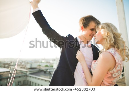 Young couple in love posing on roof with perfect city view holding hands and hugging . Beautiful sunset - stock photo