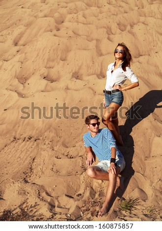 Young couple in love posing outdoor in sand in summer weather and having fun - stock photo