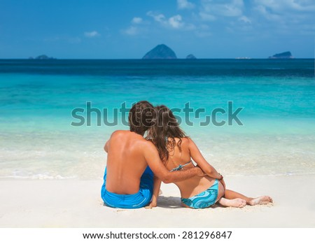 Young couple in love relaxing on vacation enjoying ocean view on the tropical beach - stock photo