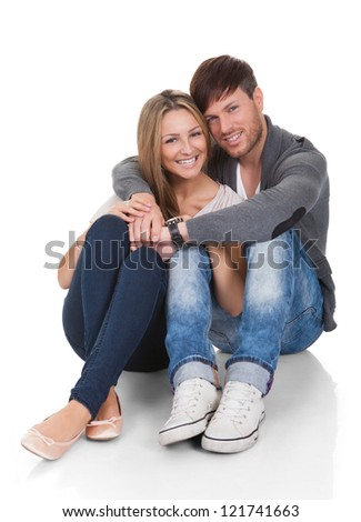 Young couple in love sitting close together on the floor in an affectionate embrace smiling at the camera - stock photo