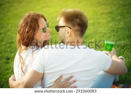 Young couple in love sitting in the summer park face to face. Beautiful people in sunglasses in the picnic resting. - stock photo
