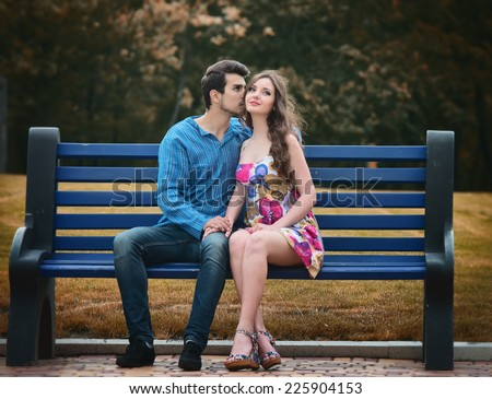 Young couple in love sitting together on the bench in the park - stock photo