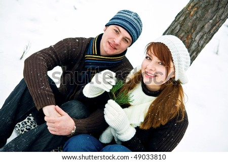 Young couple in love smiling in winter - stock photo