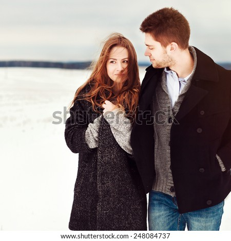 Young couple in love walking in cold winter field and getting cold but feels happy together  - stock photo