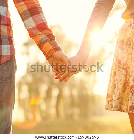 Young couple in love walking in the autumn park holding hands looking in the sunset - stock photo