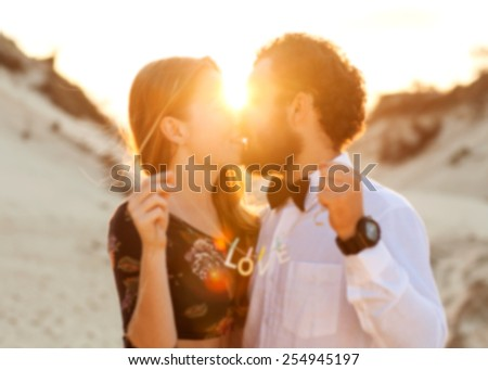 Young couple in love walking in the  park holding hands looking in the sunset, blurry photos -Concept - stock photo
