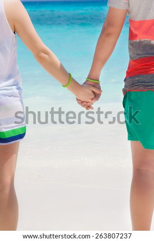 Young couple in love walking on the beach holding hands at Similan island, Thailand. - stock photo